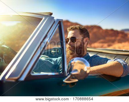 bearded guy in desert sitting in cool vintage car shot with lens lens