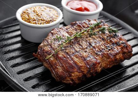 cooked steak on the grill pan on the steak is herb thyme there are a number sauces - ketchup and mustard French