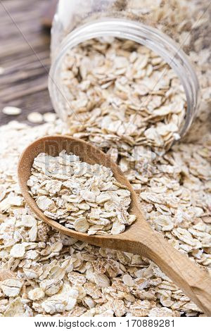 raw oatmeal is scattered on the desk of the bank in which the oat flakes are stored