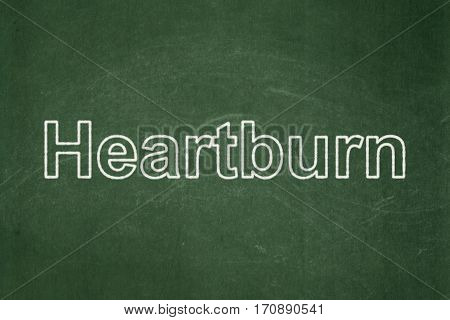 Healthcare concept: text Heartburn on Green chalkboard background