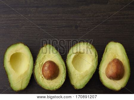 Avocado halves placed in a row on a wood surface