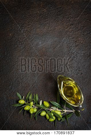 Top view of branch with green olives and glass sauceboat of olive oil on a black grunge metal background with copy space.