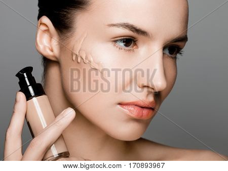 Beauty fashion model girl holding foundation tube container with foundation on her cheek on grey background
