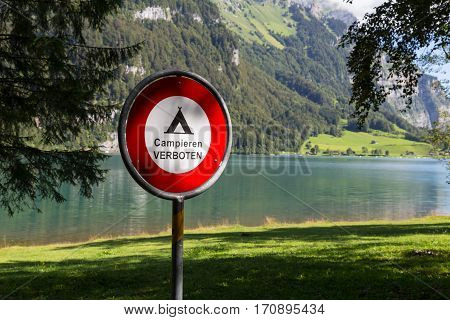 Round iron prohibition sign near the lake on background of mountains. Alps. Switzerland