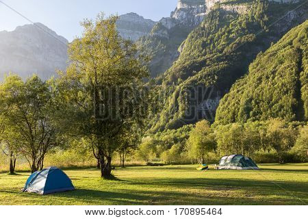 Two tourist tents in the forest against majestic mountains lit by the morning sun. Alps. Switzerland.