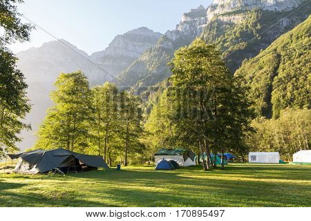 Camping on the against majestic mountains lit by the morning sun. Switzerland.