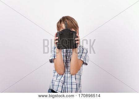 Young boy holding a drone remote control in front of his face