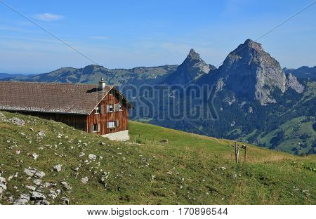 Summer scene in Switzerland. View from Stoos mount Mythen. Farmhouse and green meadow.
