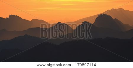 Golden sunrise in the Swiss Alps. Outlines of mountain ranges. View from mount Rigi.