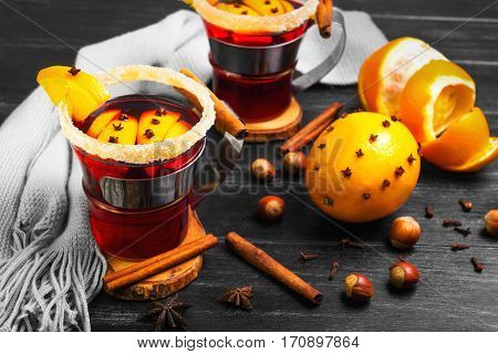 Traditional Christmas winter beverage drink mulled wine on Dark Black background. Glasses with mulled wine wrap knit scarf. Ingredients for mulled wine hazelnut cinnamon cloves orange star anise.