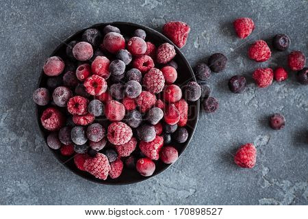 Frozen raspberry blueberry cranberry on grunge background. Frozen fruit. Top view close up