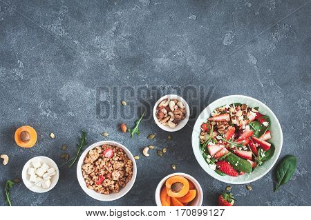 Breakfast with muesli strawberry salad fresh fruit nuts on grunge background. Healthy food concept. Flat lay top view