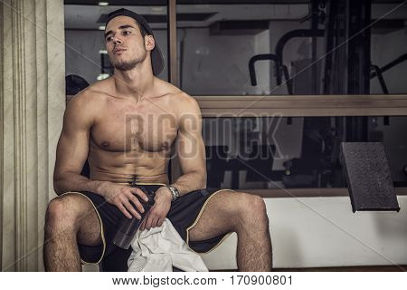 Muscular, shirtless young man resting in gym during workout, showing muscular torso, pecs and abs, holding a towel in his hands, sitting on bench