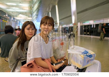 SINGAPORE - CIRCA NOVEMBER, 2015: indoor portrait of two women in MRT station at Changi Airport. MRT, is a rapid transit system forming the major component of the railway system in Singapore.