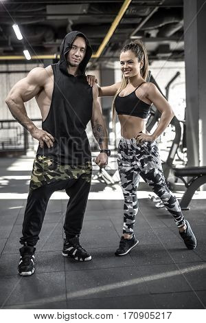 Smiling couple stand in the gym. Girl wears multi-colored pants with a black top and sneakers, guy wears dark pants with a black hooded sleeveless and sneakers. They look into the camera. Vertical.