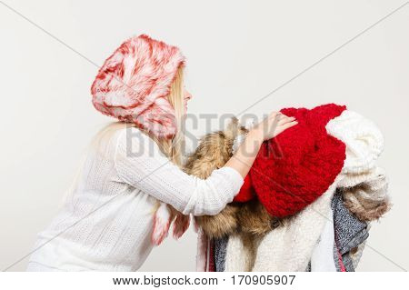Woman In Winter Hat Holding Pile Of Clothes