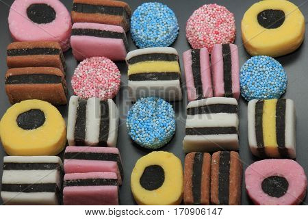 Stacked liquorice all sorts in different shapes colors and sizes
