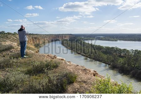Nildottie South Australia Australia - August 13 2016: Male middle aged photographer looking down on the Murray River near Nildottie from the top of the cliffs Murraylands region of South Australia