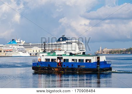 HAVANA,FEBRUARY 6,2016 : An old motorboat carries passengers across the bay of Havana with modern cruiser ships on the background