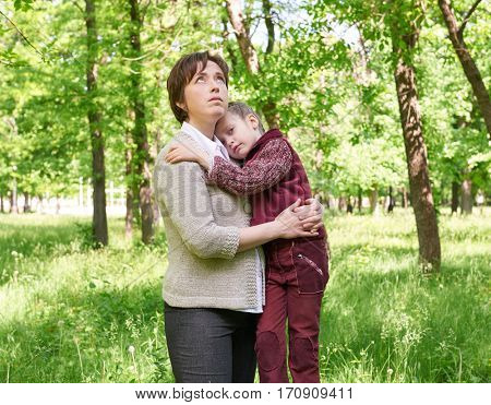 dreamy mom and daughter in summer park, sunlight, green grass and trees