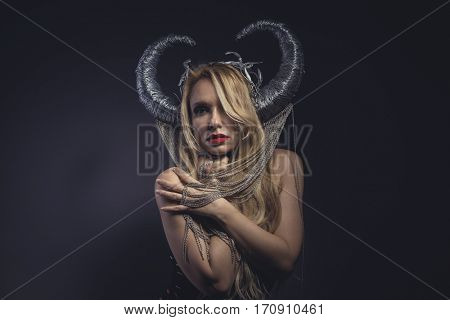Viking goddess, beautiful young blond woman with horned helmet made of iron. Fantasy image and stories