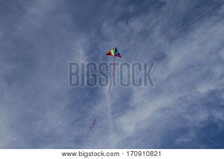 Recreational, Kite of rainbow colors on a blue sky with light white clouds