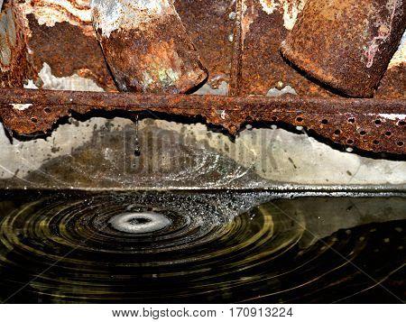 Tubería oxidada goteando y salpicando sobre agua.