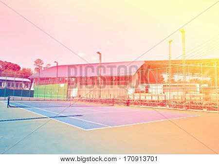 Outdoor hard court tennis against blue sky