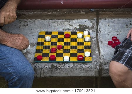 ALAJUELA, COSTA RICA - January 23: Old men play checkers with bottle caps. January 23, 2016 in Alajuela.