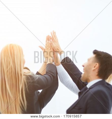 at the bottom of the photo - successful business team standing in a circle and together raised their hands on a white background. in the top of the photo is empty space for your text