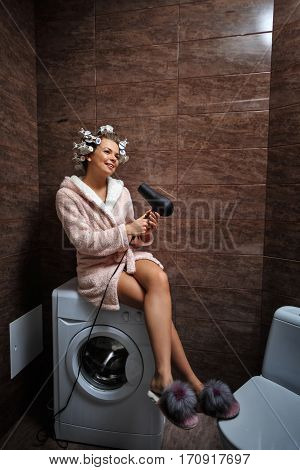 Young attractive housewife in the bathroom. A girl in a bathrobe and curlers in hair sings in a microphone. Great morning.