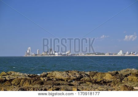 The skyline of the resort area of Mazatlan is visible against the blue sea waters.