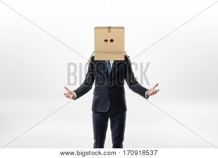 Businessman is staying his hands to the sides with a box on his head with holes for eyes on white background. Business relationship. Unknown future. Searching for decisions