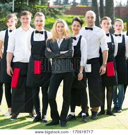 group of waiters in the branded clothes are on the lawn in front of a prestigious restaurant