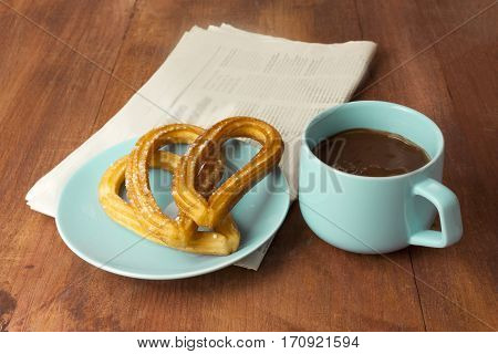 Plate of churros, traditional Spanish, especially Madrid, dessert, particularly for Sunday breakfast, with cup of hot chocolate and blurred newspaper