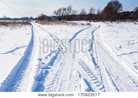 The Fork snowy winter road with traces from cars in winter bright day. Countryside, Landscape