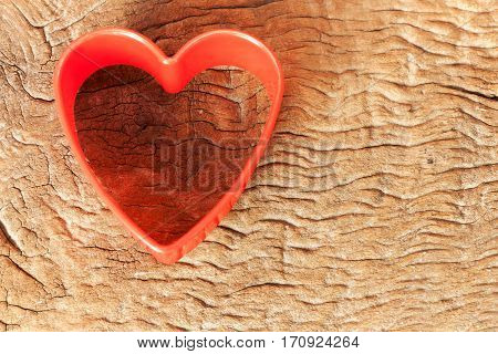Idea for card Valentine day. Heart shaped cookie cutter on old wood background