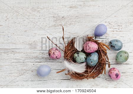 Easter background with painted easter eggs in nest vintage style, top view.