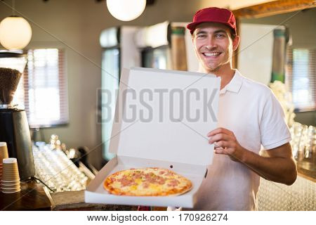Portrait of pizza delivery man showing fresh pizza
