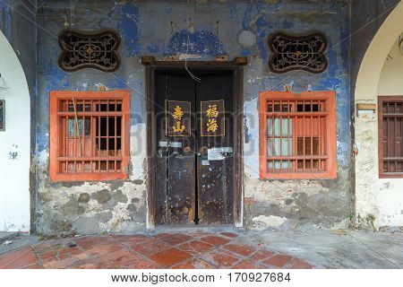 Old Run-Down Peranakan style home exterior with Chinese text Longevity Mountain and Properous Sea on wooden doors entrance