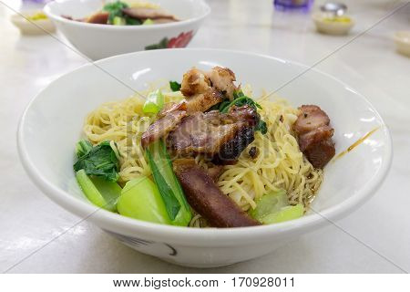 Char Siew Barbecue Pork Wanton Noodles with green vegetable dried on table version closeup macro