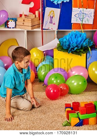 Children playing in kids club indoor. Lesson in primary school. Kindergarten child sit on floor with balloon