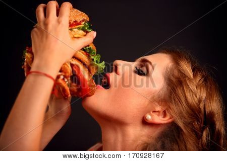 Woman eating hamburger. Student consume fast food. Girl opened her mouth to take bite of hamburger. Girl trying to eat giant sandwich. Advertise fast food on black background.