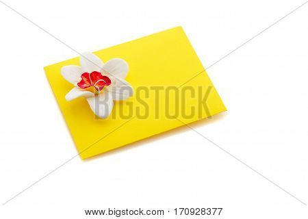 Closeup shot of small yellow envelope decorated with art clay narcissus. Handmade paper work. Copy space. Isolated over white background.