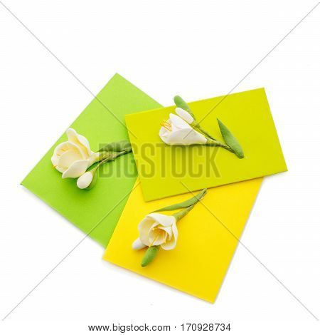 Closeup shot of three small yellow envelopes decorated with art clay tulips. Handmade paper work. Copy space. Isolated over white background. Square composition.