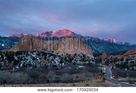Pikes Peak Mountain glows in the sunrise at Garden of the Gods in Colorado Springs Colorado