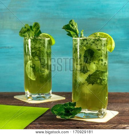 A square photo of mojito cocktails with mint leaves and wedges of lime, on a vibrant teal wooden background with copy space. Selective focus