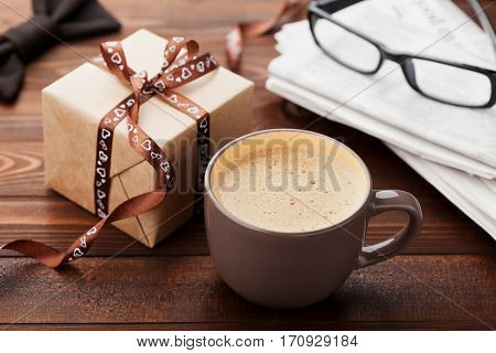 Morning cup of coffee, gift, newspaper, glasses and bowtie on wooden desk for breakfast on Happy Fathers Day.