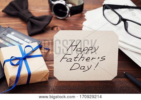 Gift or present box, newspaper, glasses, watch, bowtie and notes Happy Fathers Day on wooden table.
