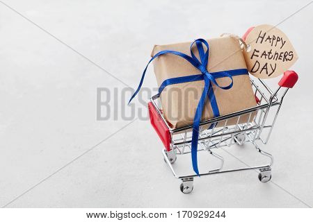 Gift or present box and notes Happy Fathers Day in shopping cart on light background.